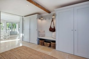 Inside entrance to a home, a bench and two coat closets